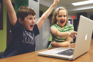 Enfants joyeux devant un écran de pc portable